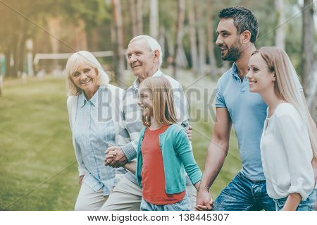 Family time. Happy young family holding hands while walking outdoors together