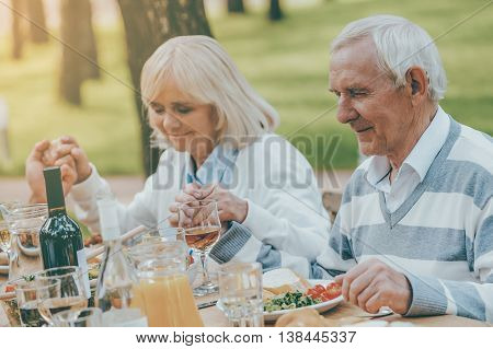 Thanking God for meal. Senior couple holding hands and praying before family dinner while sitting at the table outdoors