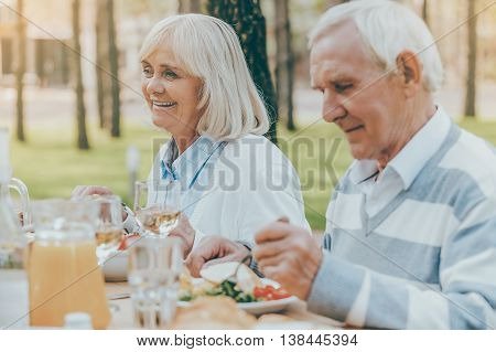 Enjoying dinner on fresh air. Senior couple enjoying meal together while sitting at the dining table outdoors
