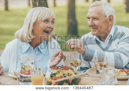 The best for our nearest. Senior man feeding his cheerful wife with fresh salad while both sitting at the dining table outdoors