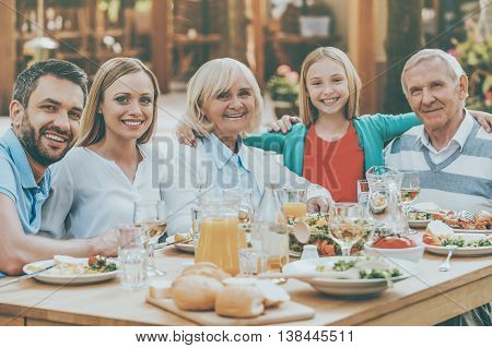 Family gathering concept. Happy family of five people bonding to each other and smiling while sitting at the dining table outdoors