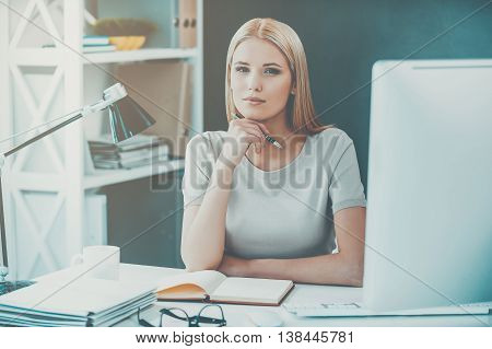 Young and confident. Beautiful young woman holding hand on chin and looking at camera while sitting at her working place in office