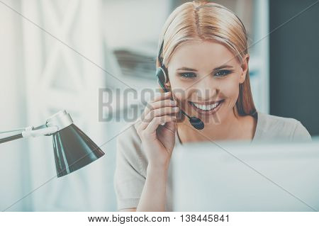 Always ready to help. Happy young woman working at the computer and adjusting her headset while sitting at her working place