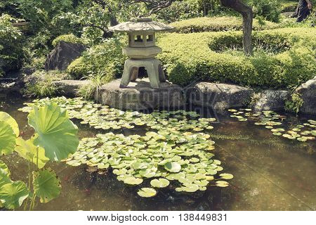 Japanese zen garden and pond with traditional stone lantern on distant shore
