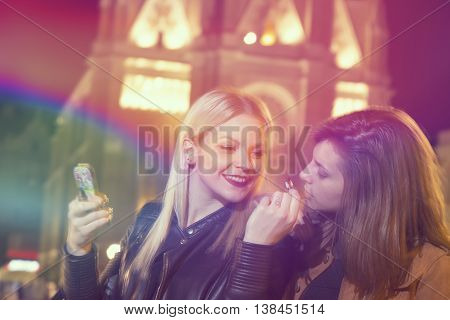 Two girl friends on a girls' night out repairing their make up and having fun on the city streets