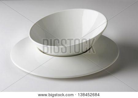 Empty Flat and asymmetrical white bowl on white table