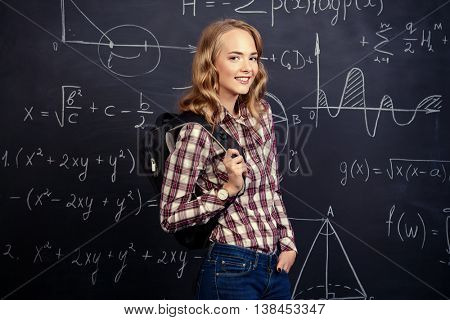 Portrait of a student girl standing by a school blackboard. Education, high school, college.