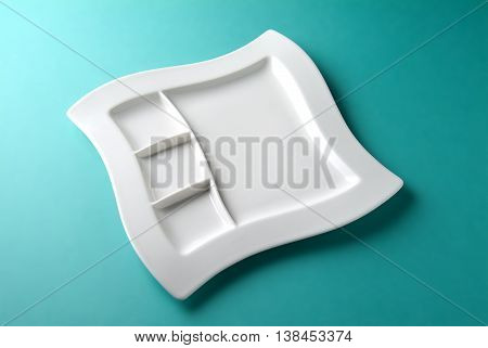 Empty white square plate with a special design on a sea-green table