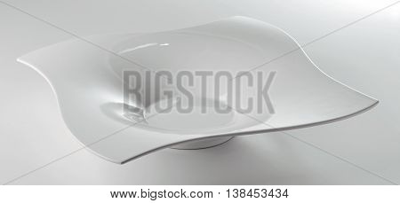 Empty white square plate with a special design on a white table
