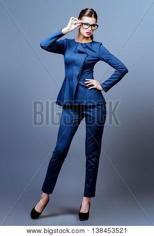 Optics style. Full length portrait of a beautiful young woman wearing elegant glasses. Beauty, fashion. Cosmetics, make-up.