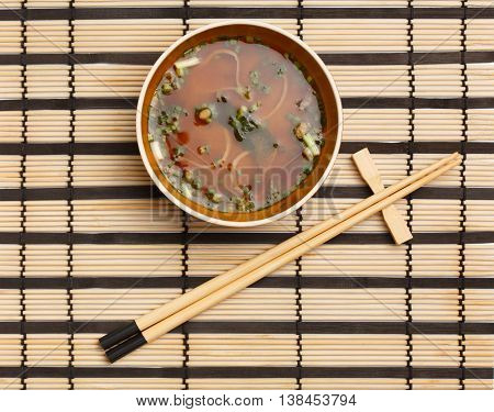 Bowl of delicious traditional japanese miso soup with wakame seaweed and tofu standing on striped bamboo mat with chopsticks lying near.