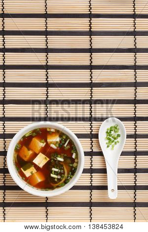 Bowl of delicious traditional japanese miso soup with tofu and wakame seaweed white ceramic spoon with chopped greens standing on striped bamboo mat.