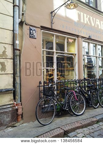 Riga, Latvia - August 4, 2013 - Old street in the center of city with two bicycles and antique shop. Summertime, sunny day.