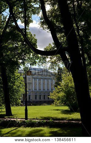 View on the park with antique palace 19th century in Saint Petersburg. Summer Michael Garden (Mikhaylovskiy Sad) in the center of the city, trees, branches, dark shadows. Selective focus, cloudy sky.