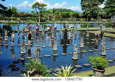 BALI, INDONESIA - 3 Jul 2015: People walking on the stepstones of Tirtagangga Water Palace in Bali Indonesia