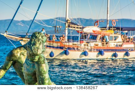Sculpture of fisherman in foreground with touristic boat in background in Island of Brac, Bol town, Croatia.