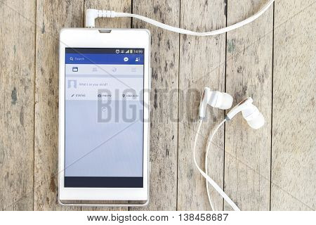 BUNG KAN THAILAND - MARCH 22 2016: smart phone display facebook app with earphones on wood background