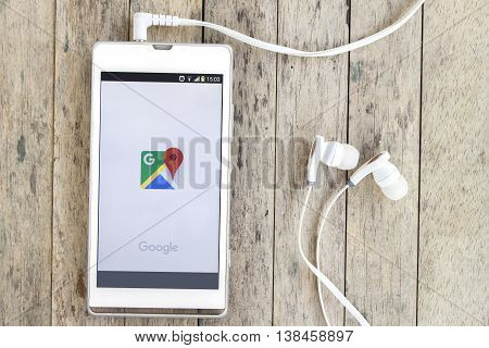 BUNG KAN THAILAND - MARCH 22 2016: smart phone display google map app with earphones on wood background