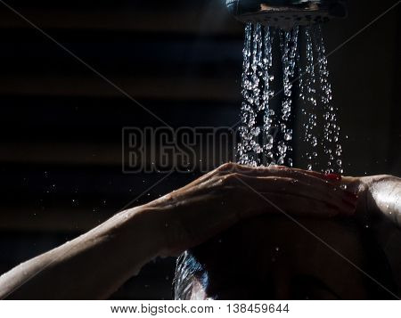 Woman under the shower with hand in the hair