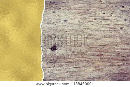 wooden background with golden torn paper and copy space