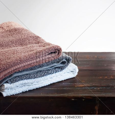 Pile Soft White Brown Gray Cotton Terry Towels on Wooden Table Light Background Closeup