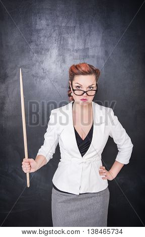 Serious Teacher In Glasses With Pointer