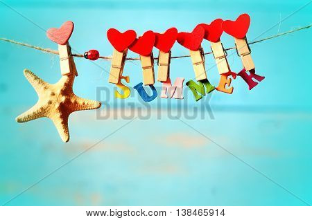 Starfish with letters hanging from clothespins on a blue background
