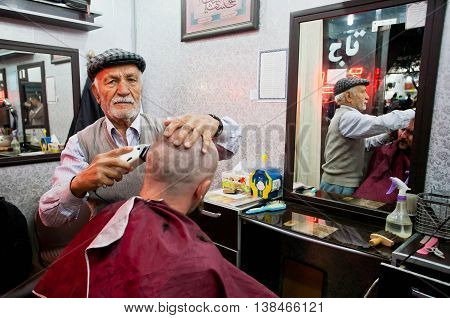 YAZD, IRAN - OCT 20, 2014: Elderly barber cuts and shaves the client in small hair saloon on October 20, 2014 in Middle East. Population of Yazd is near 270.600 families