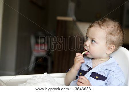Child eating lemon in a high chair