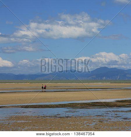 Summer scene in Marahau New Zealand. Beach at low tide. Mountains.
