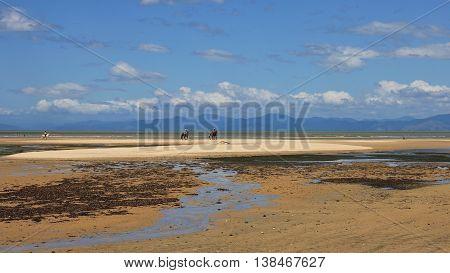 Marahau beach at low tide and mountain range. Summer scene in New Zealand.