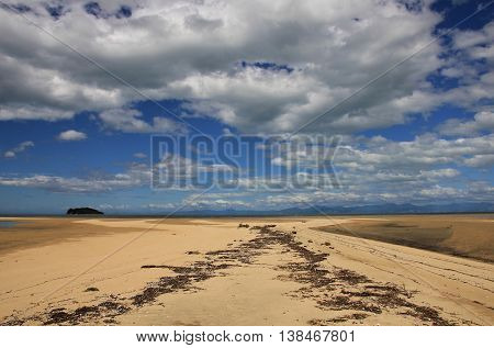 Summer clouds over sandy Marahau beach. Scene in the Abel Tasman National Park New Zealand.