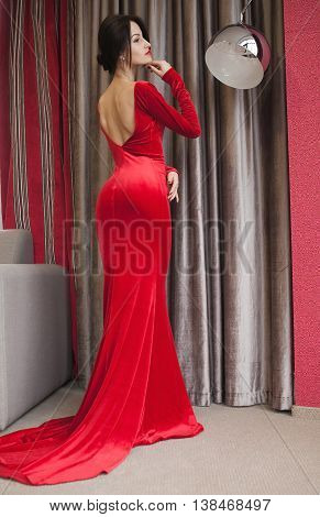 Elegant lady in red dress. Fashion beautiful sensual brunette woman with makeup in luxurious prom dress