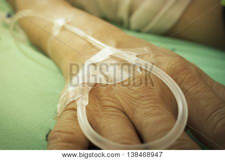 old man hand is receiving patient intravenous saline vintage tone