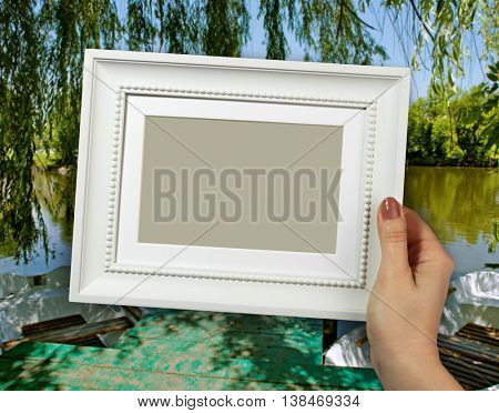 Wooden frame in beautiful woman hands. Boat at the lake on the background