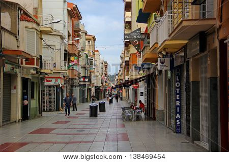 CALELLA, Spain - June 27. pedestrian street lined with tile, Spanish town, low houses, the upper floors for housing, ground floor - shops, cafes, souvenir shops