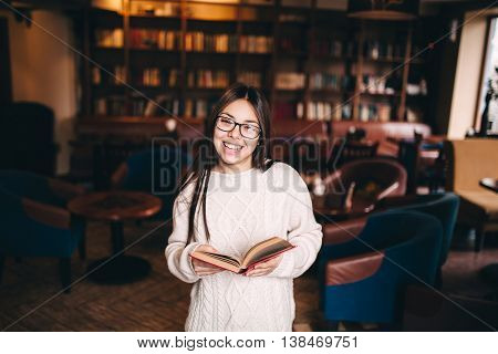 Smiling young female student laughing and holding a book in library with copy space