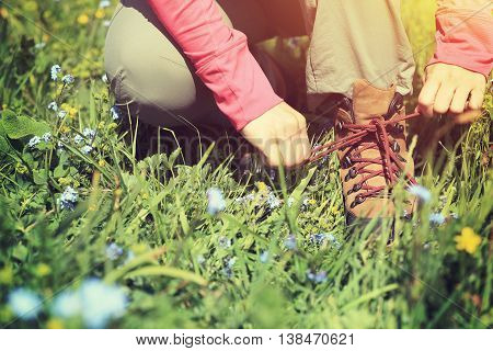 woman hiker tying shoelace on grassland grass