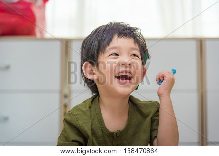 Close up of cute asian child holding crayon and drawing on white paper.