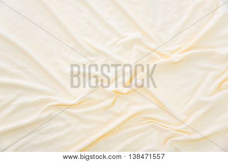 Close up of wrinkled beige color bed sheet texture background.
