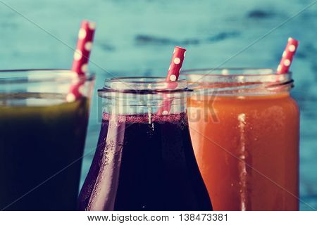 closeup of three different fresh smoothies served in a glass, a glass jar and a glass bottle with red drinking straws patterned with white dots, against a blue rustic wooden background