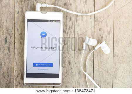 BUNG KAN THAILAND - MARCH 22 2016: smart phone display facebook messenger app with earphones on wood background with sunlight