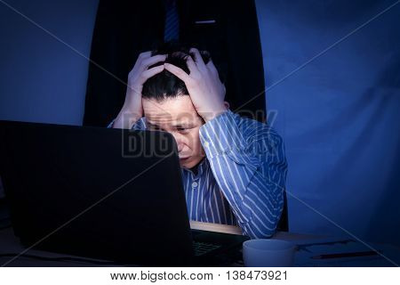 Overworked office worker sitting beside desk at office, at night and very stress