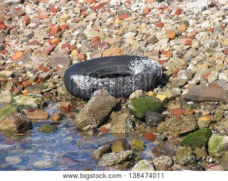 Old Car Tyre, Broken Bricks And Other Junk At The Waters Edge.