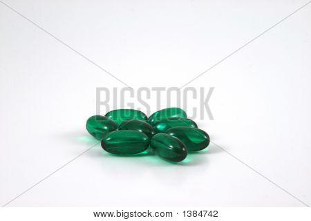 Grüne Kapseln auf weißem Hintergrund