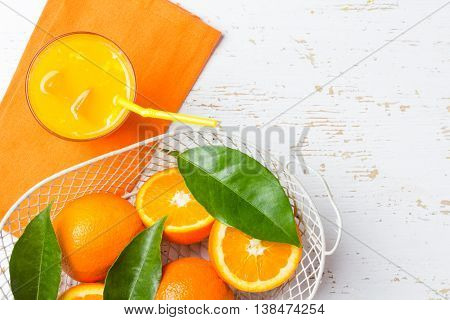 Glass of freshly squeezed orange juice, fresh oranges ib basket and leaves on white background. Top view