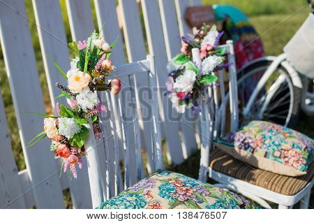 Beautiful open terrace in the garden with tiffany coloured vintage white chairs, colorful velvet pillow and fence palisade, bicycle on background decorated flowers in boho style