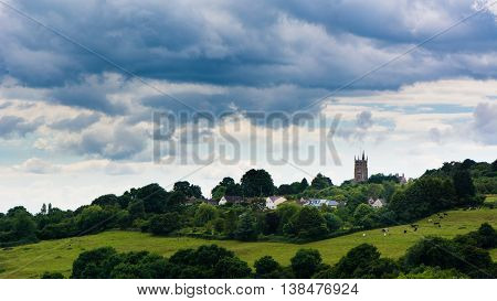 Landscape and Church of St. John the Baptist, Colerne, Wiltshire. Parish church within a rural English landscape with fields and grazing cattle and cloudy sky