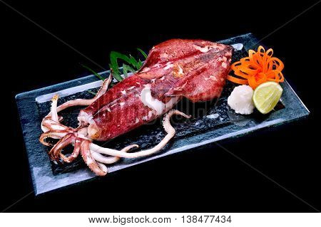 Japanese grilled squid full body in glass plate photo in studio lighting.
