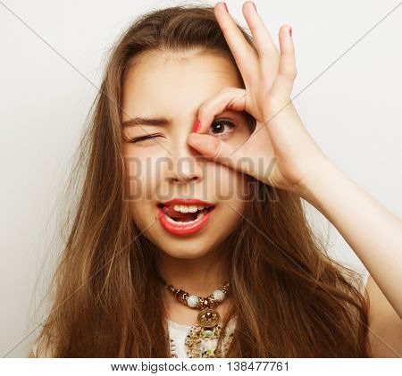 Pretty young woman looking for something with wide open eyes and imaginary binocular.